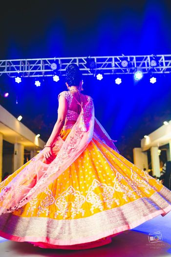 Bride twirling on sangeet in yellow lehenga