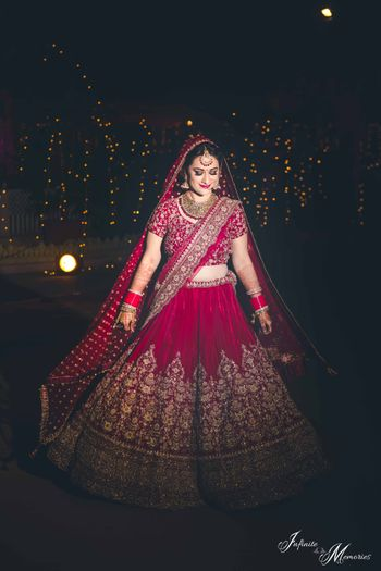 Photo of Bride posing in deep red bridal lehenga at night