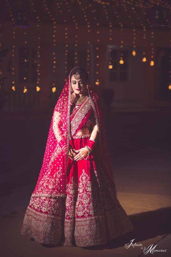 Bride posing in deep red bridal lehenga with threadwork