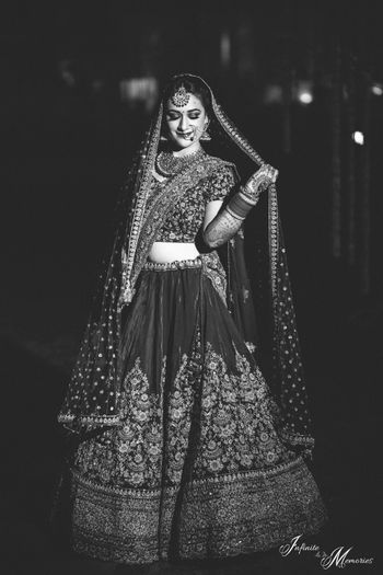 Black and white bridal portrait with bride holding dupatta