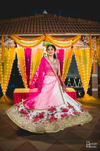 Bride twirling in pink and white floral lehenga