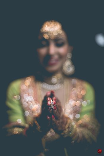 Bride holding engagement ring in focus