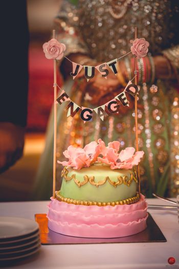 Pastel wedding cake with cute cake topper