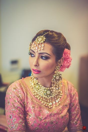 Bridal hair and makeup with light pink lehenga