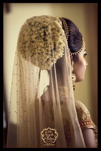 Photo of Bridal bun with flowers and attached dupatta