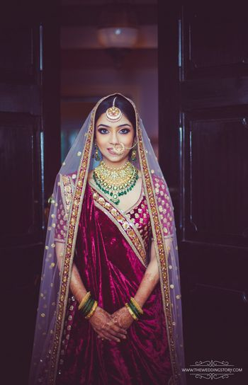 Photo of Maroon bridal lehenga with green contrasting jewellery