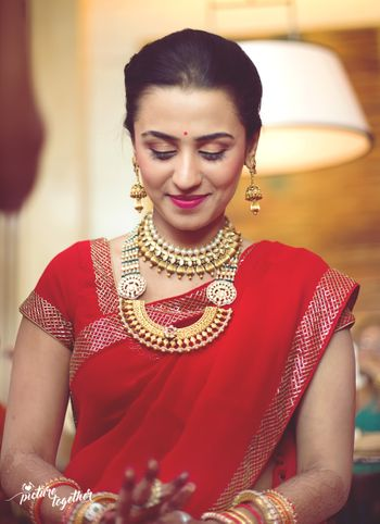 Bride in red saree and layered necklaces