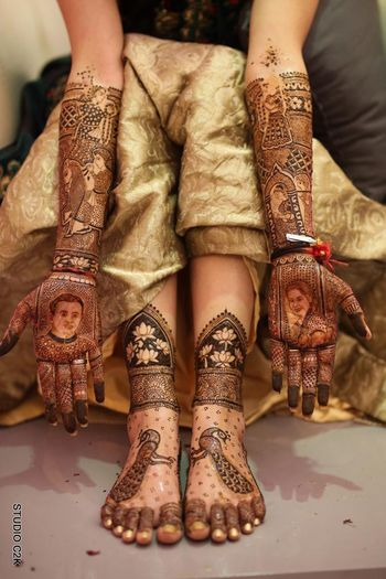 Hand mehendi with portraits and feet with peacock motifs