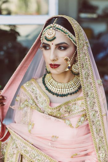 Photo of Bride posing in light pink lehenga and contrasting green jewellery