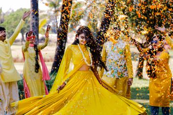 Photo of Bride twirling on haldi in yellow outfit