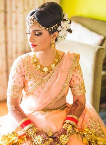 Photo of Gold bridal jewellery with light pink lehenga