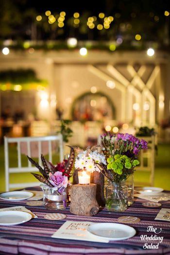 Photo of Table setting with flowers in glass jars and candles