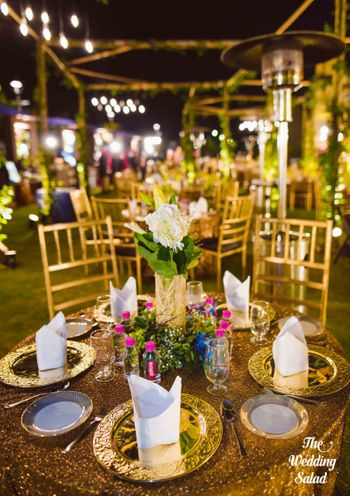 Photo of Pretty table setting with floral table centerpiece and gold plated cutlery
