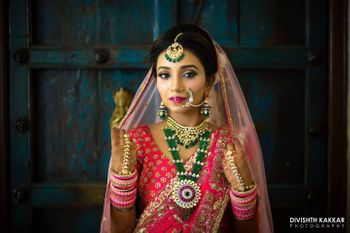 Pink bridal lehenga with green contrasting jewellery