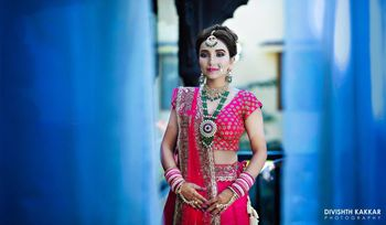 Red bridal lehenga with contrasting green jewellery