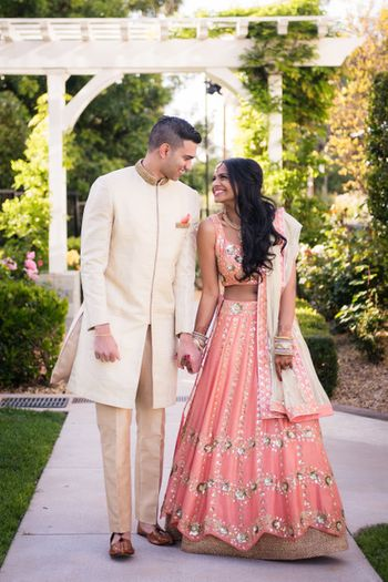 Couple portrait in peach engagement lehenga