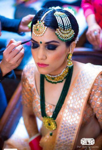 Bride with black smokey eyes and peach lehenga