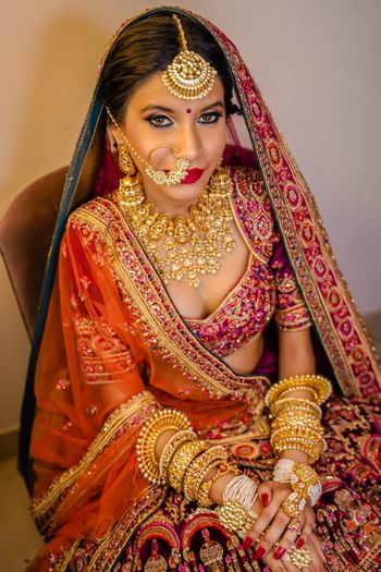 A bride in a multicolored lehenga with heavy gold jewellery