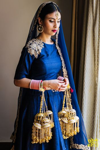 Minimal bride wearing blue lehenga and kaleeras