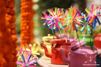 Photo of Colorful paper wheels and tea kettle in mehendi decor