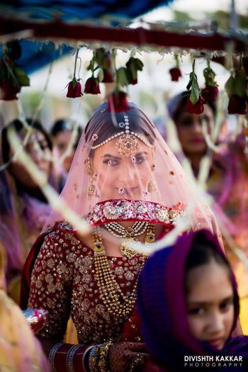 Bride entering wearing dupatta as veil