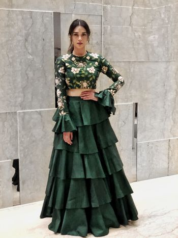 Beautiful bottle green lehenga with bell sleeved blouse and floral print along with a layered lehenga skirt