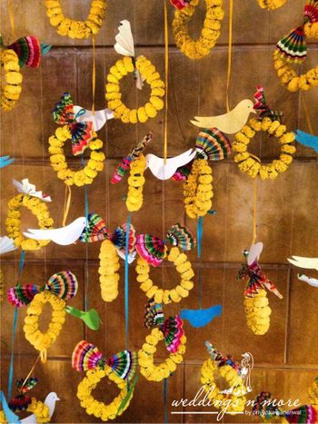 Mehendi decor idea with hanging genda phool rings and bird cutouts
