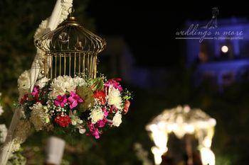 Gold birdcage with flower arrangement