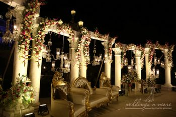Elegant stage decor with flowers and candle lit chandeliers