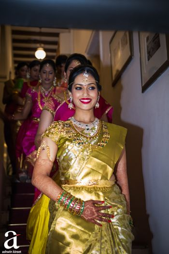 Photo of South Indian bride stepping down the stairs with bridesmaids
