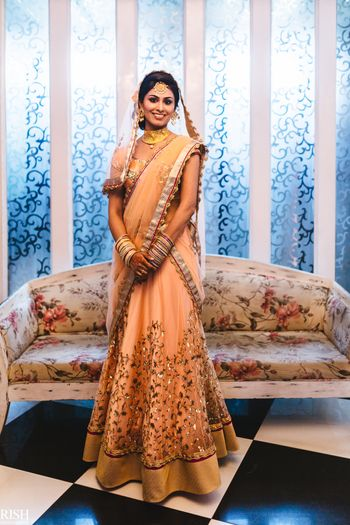 Bride in peach minimal lehenga with gold motifs