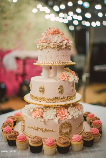 3 tier white and peach wedding cake with gold details
