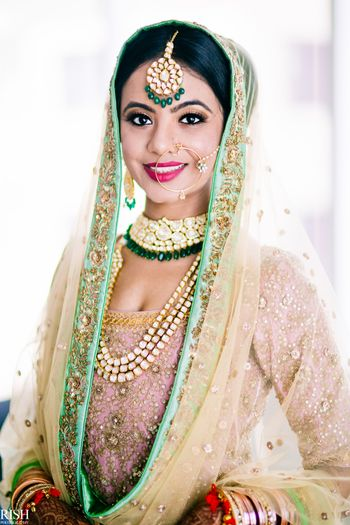 Pastel bride wearing contrasting jewellery with green beads