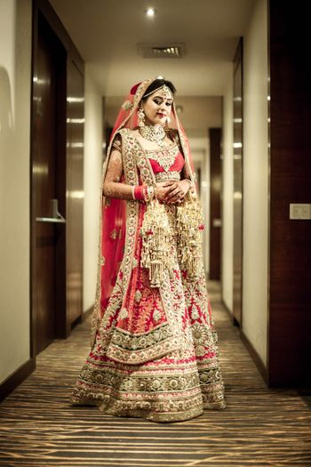 Classic red and gold bridal lehenga with heavy gold work and detailings