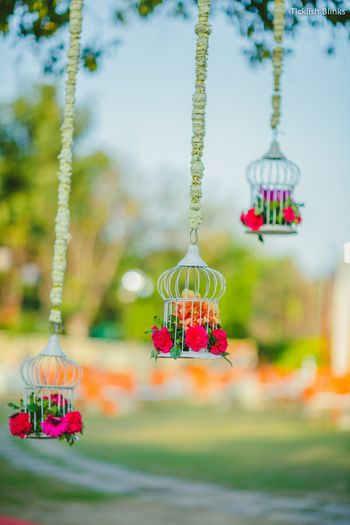 Hanging birdcage with floral arrangement