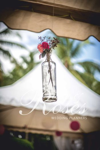 Hanging glass bottle with flowers in decor