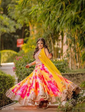 Photo of Bride twirling in pink and yellow tie and dye lehenga