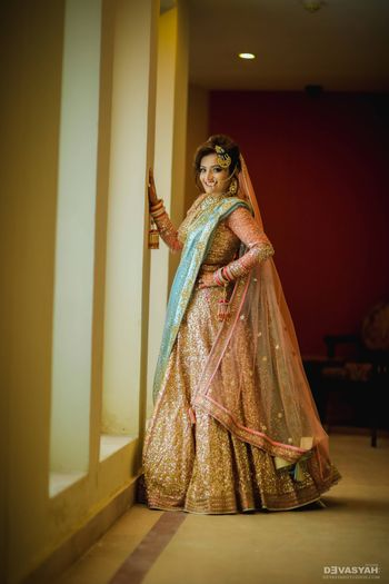 Photo of Rose gold sabysachi lehenga with baby blue dupatta