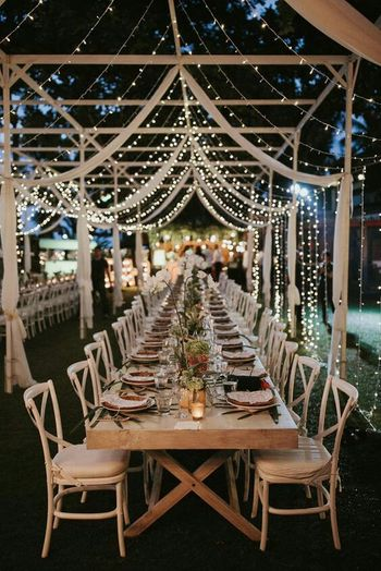 Long table setting for intimate event with fairy lights