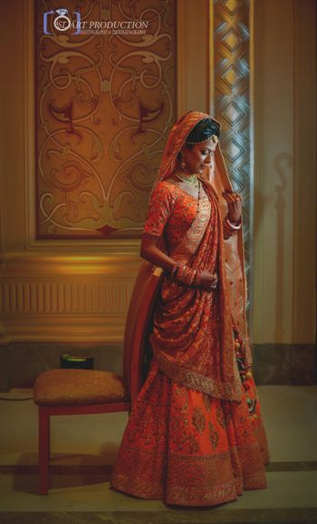 Photo of Gorgeous bridal lehenga in orange and gold