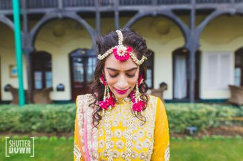 Bride in bright pink and white floral jewellery on mehendi