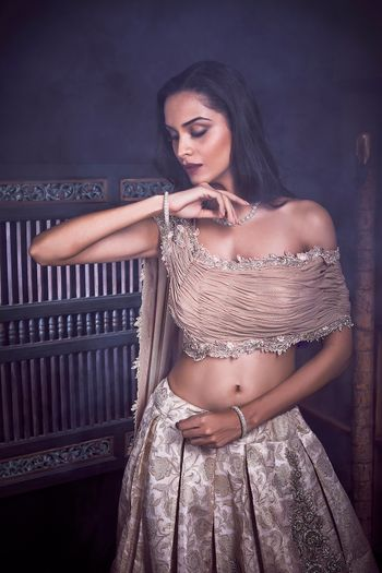 Modern lehenga in dull gold with off shoulder blouse