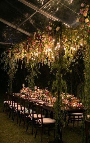 Beautiful outdoor sit down dinner set up with floral and lighting