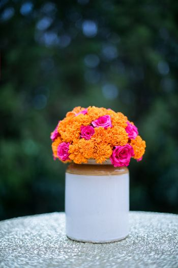Cute marigold and rose centrepiece in pickle jar