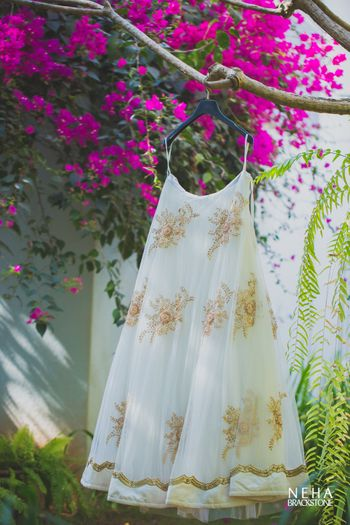 Parsi wedding lehenga on hanger in white and gold