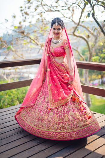 Bride twirling in coral lehenga with gold embroidery