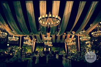 Night decor with white draped ceiling and candle lit chandeliers