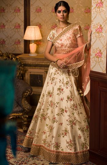 White floral lehenga with gold borders and peach dupatta for mehendi