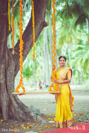 Bright and happy south Indian bride posing with floral swing on wedding day