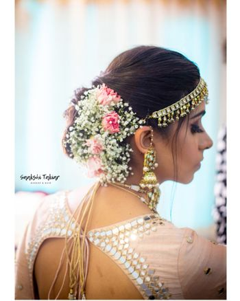 A bride with baby breath and pink roses in her hair on her wedding day